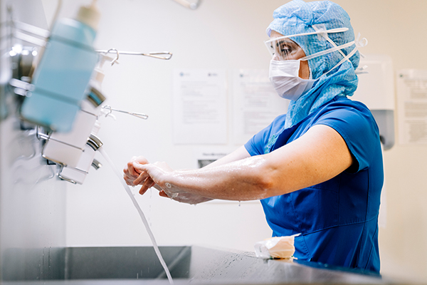 A physician wearing PPE washing their hands